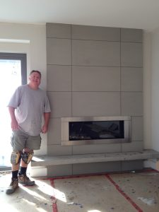 Elton Huard proudly stands by a fresh installation of Solus Concrete Panels